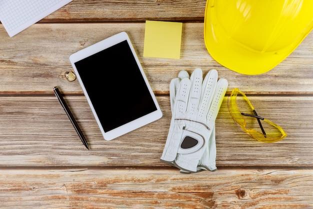 Architekt inżynier pracy standardowe wyposażenie bezpieczeństwa konstrukcji na rękawice żółty kask i tablet pc