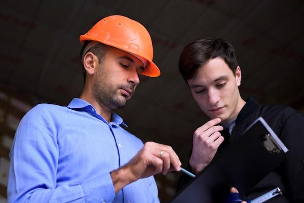 Architekt inżynier w pomarańczowym kasku w miejscu pracy, wyjaśniając klientowi plany projektu