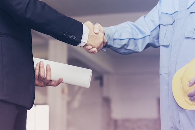 Architekt inżyniera uścisk dłoni z biznesmenem na miejscu