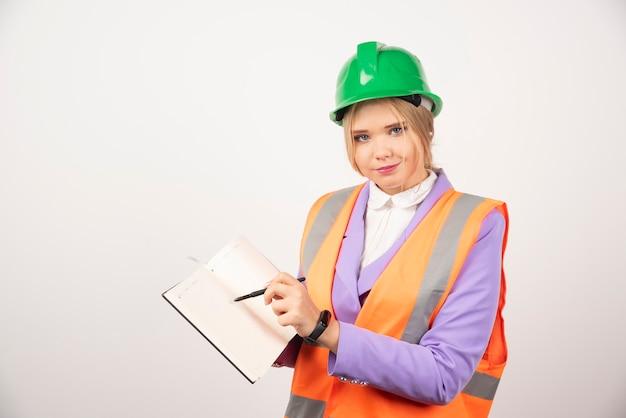 Architekt kobieta w kasku z tabletem na białym.