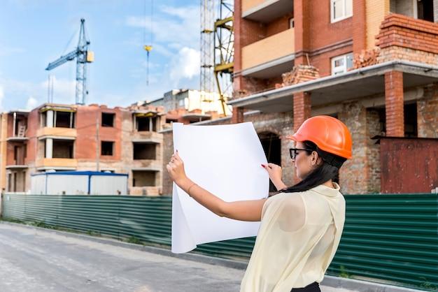 Architekt kobieta w pomarańczowym kasku z rysunkiem w pobliżu placu budowy