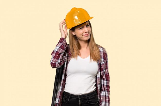 Architekt kobieta z wyrazem frustracji i niezrozumienia nad izolowanym żółtej ścianie