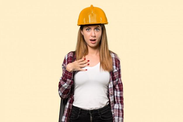 Architekt kobieta zaskoczona i zszokowana, patrząc jednocześnie na pojedyncze żółte ściany