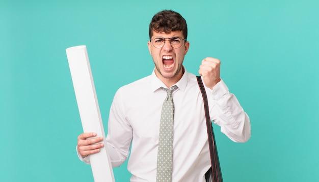 Architekt krzyczy agresywnie z gniewnym wyrazem twarzy lub z zaciśniętymi pięściami świętuje sukces