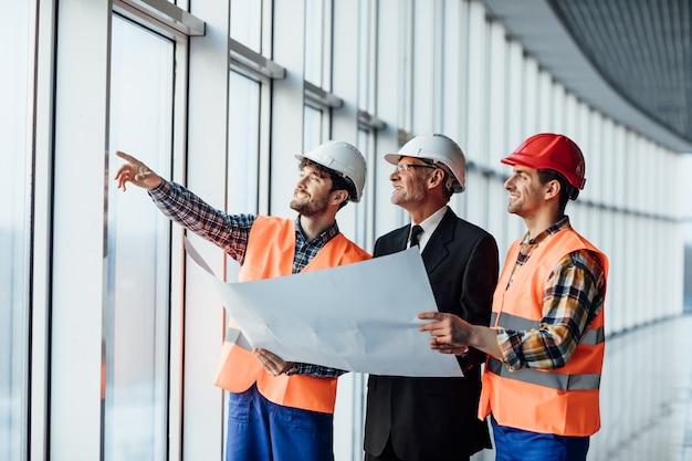 Architekt, który pokazuje coś na projekcie swojemu koledze brygadziście
