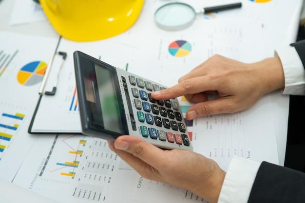 Architekt lub inżynier działający księgowość projektu z wykresem i narzędziami w biurze
