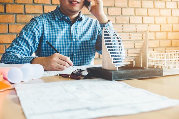 Architekt lub inżynier opowiada na mądrze telefonie pracuje w biurze na projekcie.