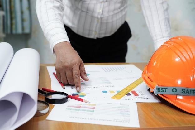 Architekt lub inżynier, pracująca księgowość projektu z wykresem w biurze.