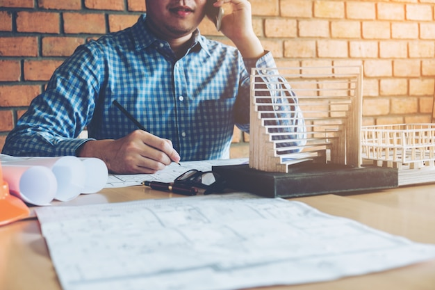 Architekt lub inżynier używa mądrze telefon pracuje w biurze na projekcie.