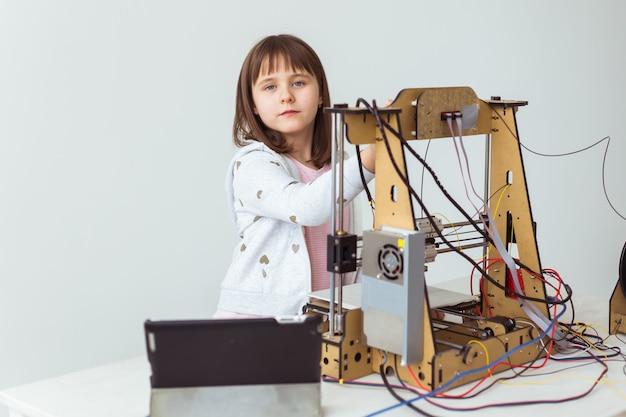 Architekt małego dziecka za pomocą drukarki 3d. uczennica, technologie i koncepcja nauki.