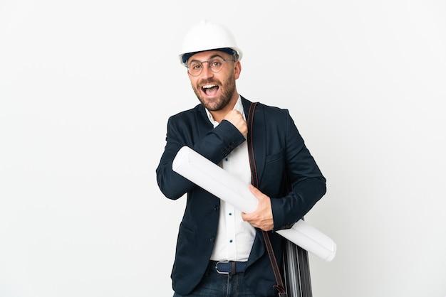 Architekt mężczyzna z hełmem i trzymający plany na białym tle świętujący zwycięstwo