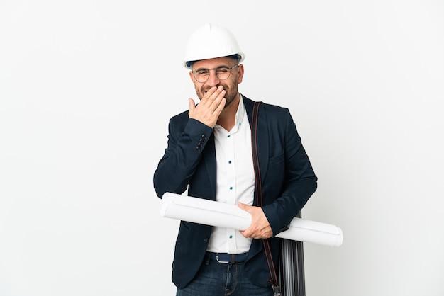 Architekt mężczyzna z hełmem i trzymający plany na białym tle szczęśliwe i uśmiechnięte zakrywanie ust ręką