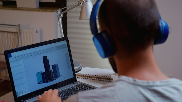 Architekt patrząc na model budynku na laptopie późno w nocy w domowym biurze. pracownik przemysłowy studiujący pomysł prototypu na komputerze osobistym pokazujący oprogramowanie cad na wyświetlaczu urządzenia pracujący w godzinach nadliczbowych