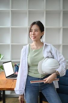 Architekt pewnie kobieta trzymając kask ochronny i stojąc w biurze.