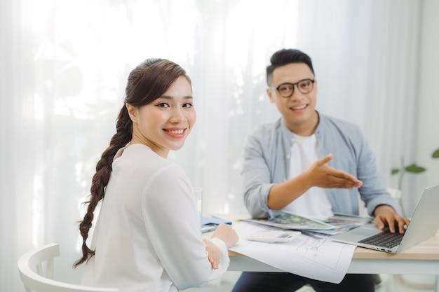 Architekt płci męskiej i żeńskiej omawiający zbiór planów rozłożonych na stole w biurze.