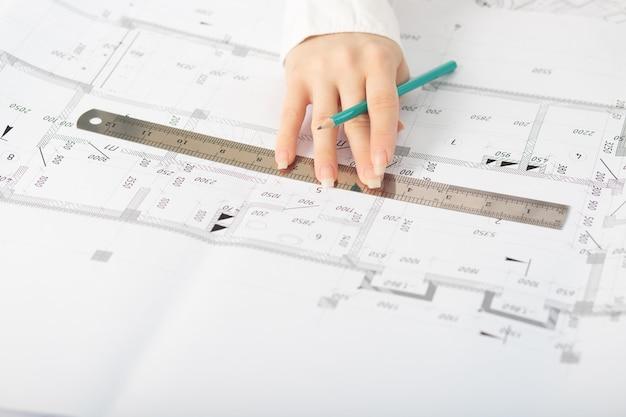 Architekt pracujący nad planem z projektem architektonicznym na budowie przy biurku