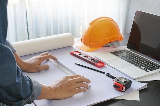 Architekt pracuje na stole z narzędziami do projektowania i budowy