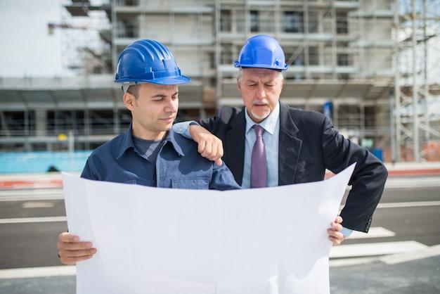 Architekt rozmawia z kierownikiem budowy przed budynkiem budowy