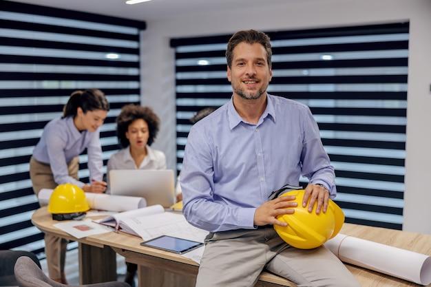 Architekt siedzi na stole w sali konferencyjnej z kaskiem w ręce.
