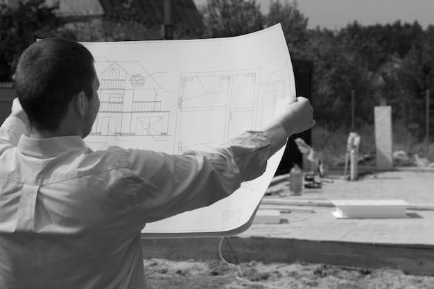 Architekt sprawdzający postęp budowy nowej konstrukcji trzymający przed sobą swój projekt, monochromatyczny obraz