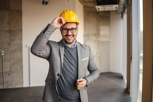 Architekt sukcesu stojąc na budowie i patrząc na kamery.