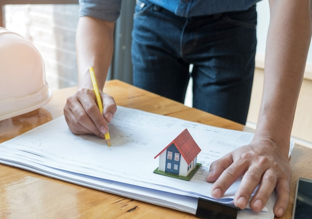 Architekt trzyma żółtego ołówkowego rysunku domu plan z modela domem na podłogowym planie.