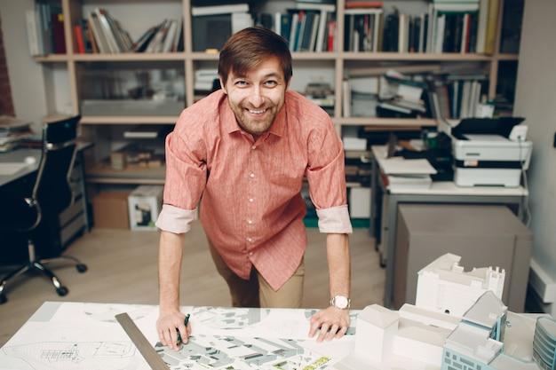 Architekt uśmiecha się z planami i projektem układu w biurze