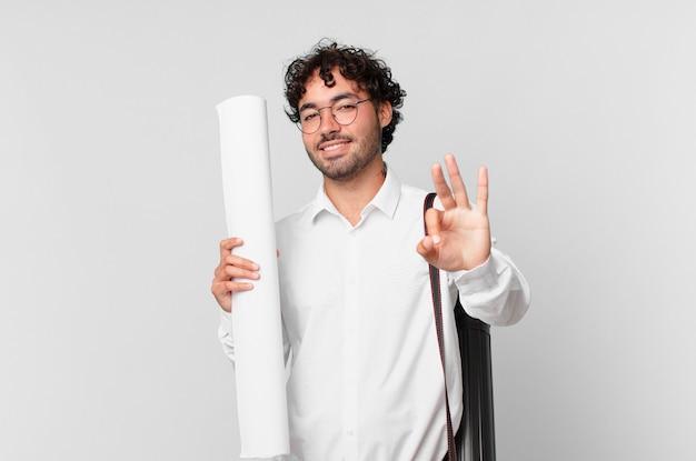 Architekt uśmiechnięty i wyglądający przyjaźnie, pokazujący cyfrę trzy lub trzecią ręką do przodu, odliczający w dół