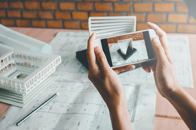 Architekt używa mądrze telefonu fotografii modela budynek w biurze.