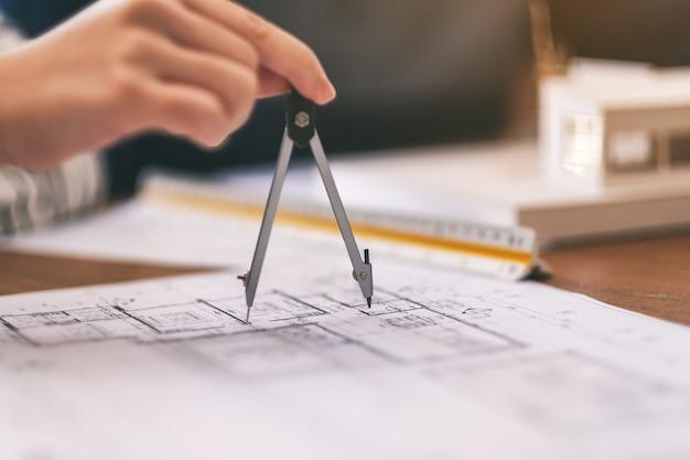Architekt używający kompasu do rysowania i mierzenia rysunku sklepowego w biurze