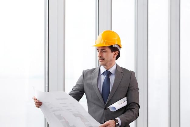 Architekt w kasku i garniturze z planami budowy