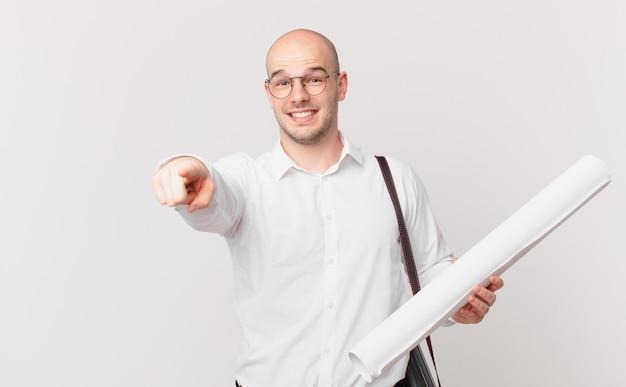 Architekt wskazujący na aparat z zadowolonym, pewnym siebie, przyjaznym uśmiechem, wybierający ciebie