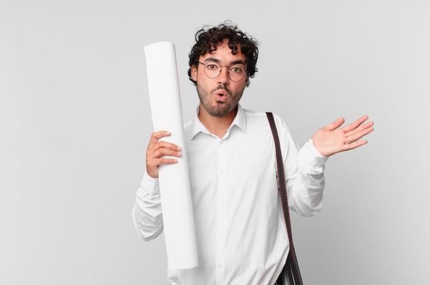 Architekt wyglądający na zaskoczonego i zszokowanego, z opuszczoną szczęką, trzymający przedmiot z otwartą dłonią z boku