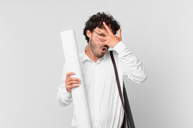 Architekt wyglądający na zszokowanego, przestraszonego lub przerażonego, zakrywający twarz dłonią i zerkający między palcami