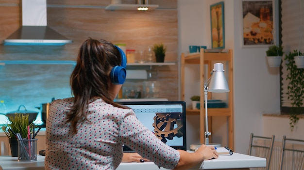 Architekt z bezprzewodowym zestawem słuchawkowym za pomocą laptopa podczas pracy w domu w nocy siedząc w kuchni. inżynier przemysłowy kobieta studiuje na komputerze osobistym pokazując oprogramowanie cad.