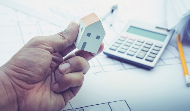 Architekt z małym modelem domu pod ręką i projektem planu
