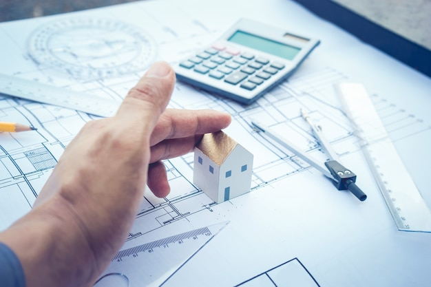 Architekt z modelem domu handlowego pod ręką i projektem planu