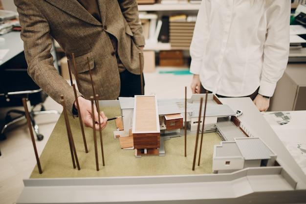 Architekt z planami i projektem układu dłoni pióra w biurze