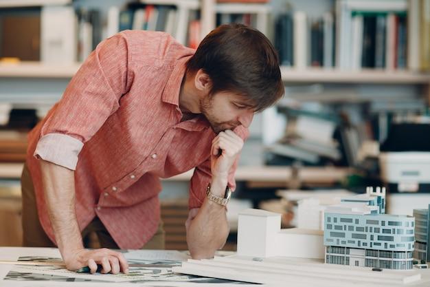 Architekt z planami i szablonem projektu układu na stole
