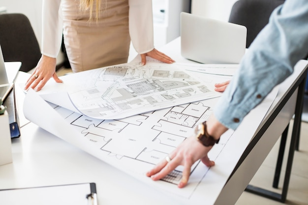 Architekta inżynier dyskutuje przy stołem z projektem