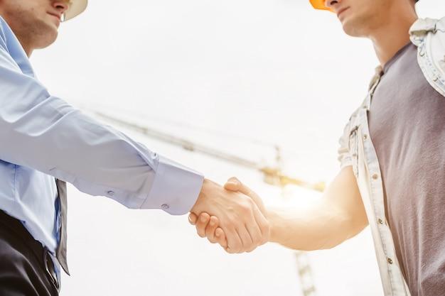 Architekta inżynier trząść rękę inną rękę na budowie. biznesowa praca zespołowa, współpraca, sukces współpracy pojęcie