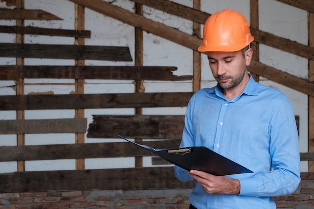 Architekta konstruktora budowlanego inżynier jest ubranym pomarańczowego hełm