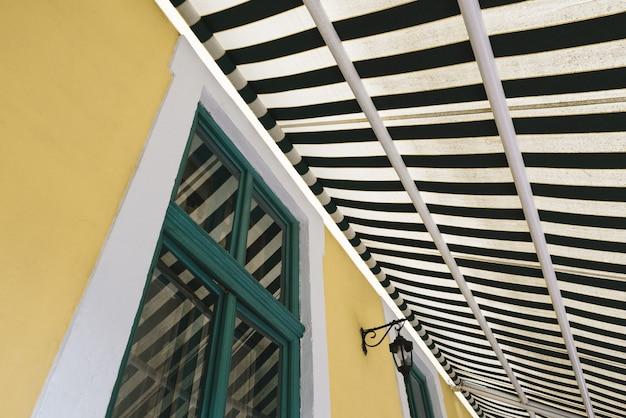 Architektoniczna abstrakcja geometryczna z oknem i markizą w paski
