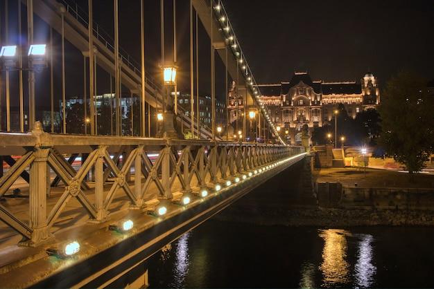 Architektoniczna konstrukcja oświetlonego starożytnego mostu łańcuchowego przez dunaj w nocy w budapeszcie na węgrzech.