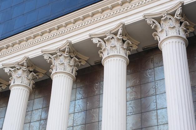 Architektoniczne białe kolumny kapitałowe na fasadzie budynku