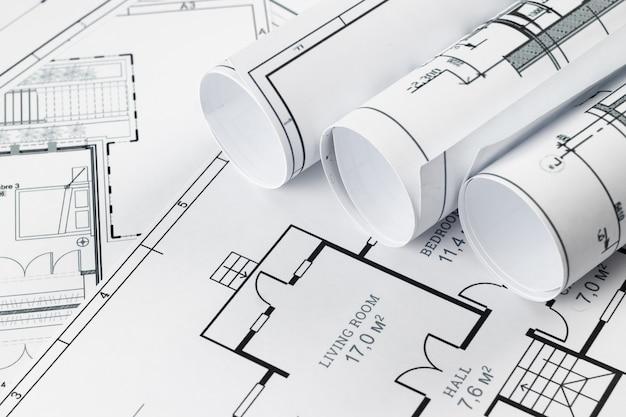 Architektoniczne rysunki konstrukcyjne skręcone w rolkę, projekty budowlane na papierze.