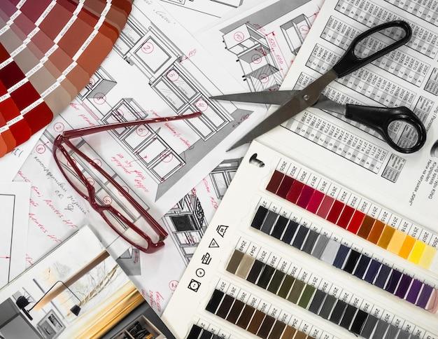 Architektoniczne wnętrze projektu z drewnianymi i papierowymi próbkami oraz wielokolorową paletą i narzędziami do rysowania