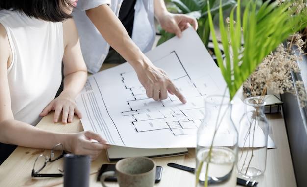 Architektura młodego mężczyzny i młodej kobiety, patrząc na plan pracy z domowego stylu życia w nowoczesnym domowym biurze, izolacja kwarantanny podczas kryzysu zdrowotnego coronavirus (covid-19)