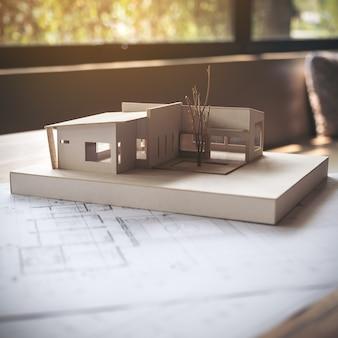 Architektura model z sklepowym rysunkowym papierem na stole w biurze