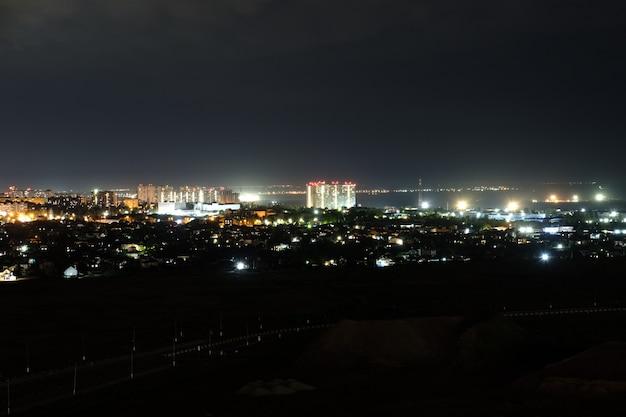 Architektura nocy. nowoczesne budynki w dzielnicy mieszkalnej na tle miasta